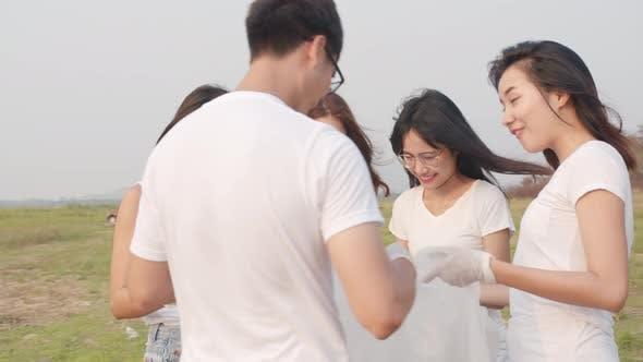 Gruppe junger multiethnischer Aktivisten, die Plastikmüll sammeln und am Strand spazieren gehen.