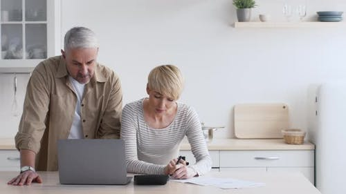 Mature Couple Calculating Expenses Taking Notes Planning Budget In Kitchen