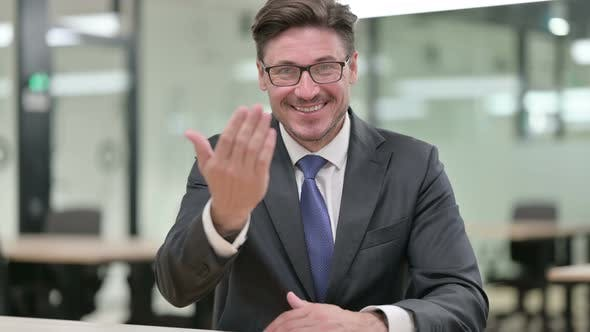 Thumbnail for Welcoming Middle Aged Businessman Pointing and Inviting