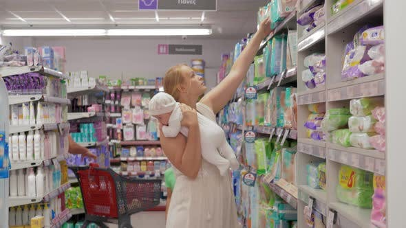 Mother Shopping with Children and Buying Diapers for Baby in Supermarket