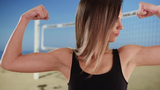 Thumbnail for Fit Caucasian girl in her 20s showing off arm muscles by beach volleyball net