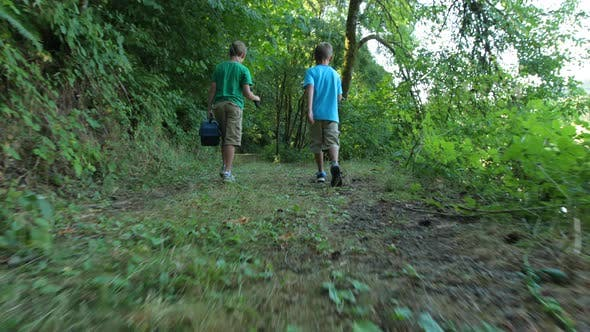 Two boys walking through woods with fishing gear