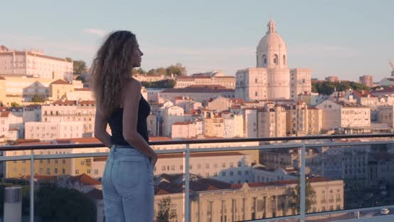 Thumbnail for Side View of Woman Which Strolls Along the Historic City of Lisbon Looking at Picturesque View