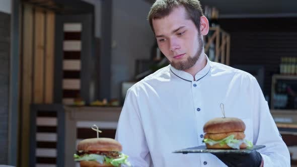 Thumbnail for Nice Waiter Makes Tasty Juicy Burgers To Joyful and Hungry Visitors of Happy Family with Children