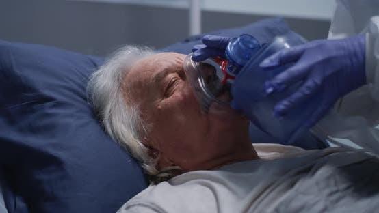 Crop Doctor Helping Elderly Man to Breath