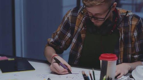 Kreativer Designer mit Kopfhörern macht Skizzen, kreativer Prozess