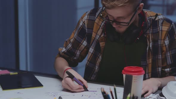 Creative Designer with Headphones Makes Sketches, Creative Process