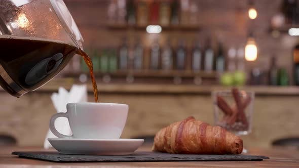 Coffee Pot Filling a Cup on a Tray with Croissant