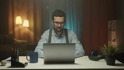 Smiling Businessman Working on Laptop Computer at Home Office