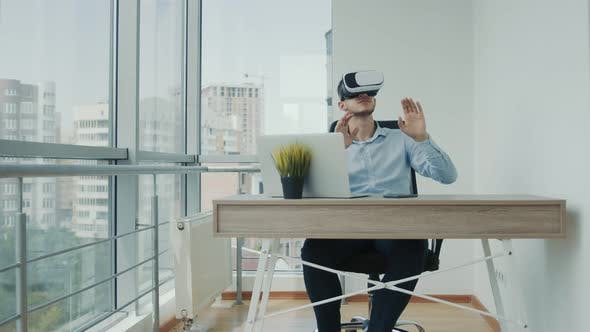 Thumbnail for A Young Man Sitting at a Desk in the Office Uses Augmented Reality Glasses To Work on Business