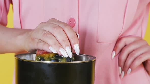 Thumbnail for Close-up of a Hand Holding a Fruit on a Juicer, Making Fresh Juice. Process of Making Fresh Juice