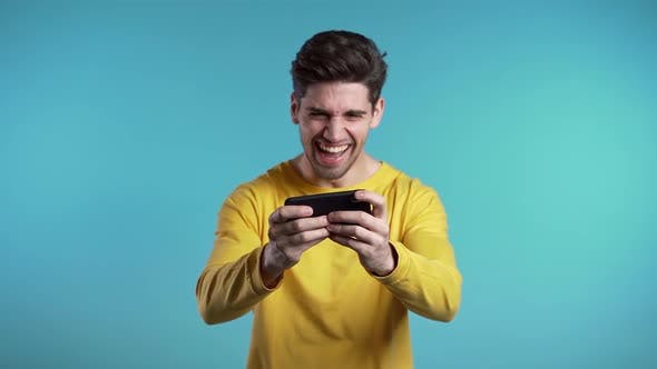 Thumbnail for Handsome man playing game on smartphone on blue studio wall.