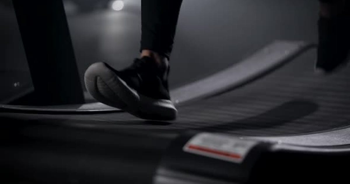In the Frame of the Athlete's Legs on a Treadmill. Running Is an Excellent Cardio Load. The Gym for