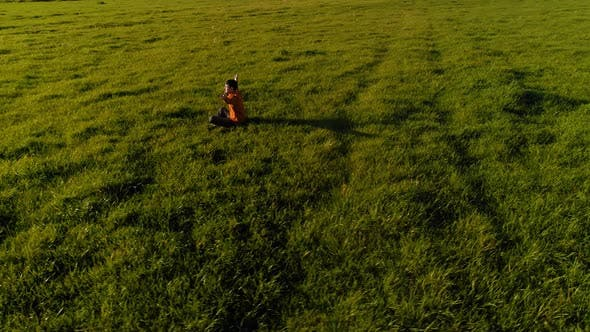 Thumbnail for Low Altitude Radial Flight Over Sport Yoga Man at Perfect Green Grass. Sunset in Mountain.