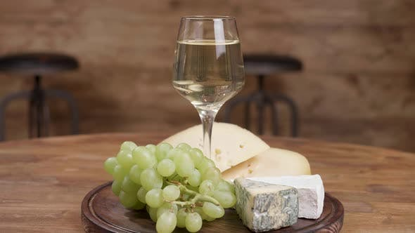 Thumbnail for A Beautiful Glass of Wine Served with Grapes and Cheeses