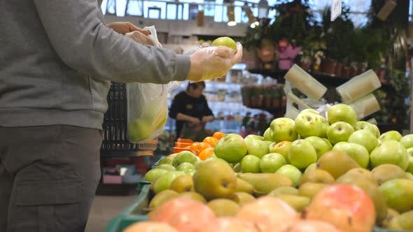 Thumbnail for Male Hands Selecting Fresh Apples in Produce Department of Grocery Store and Putting It in Plastic