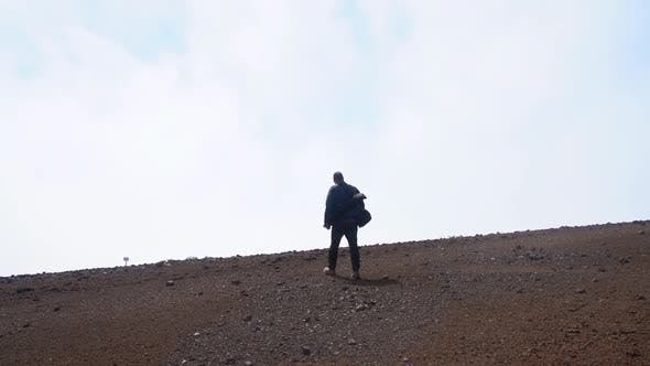 Thumbnail for Man Walking Along Stony Ground Towards Clouds