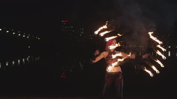 Female Artist Performing Art of Spinning Lit Fans
