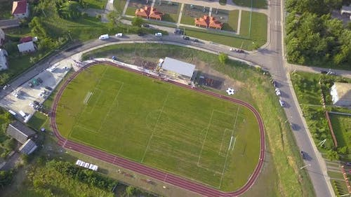 Aerial view of a football field on a stadium covered with green grass in rural town area.