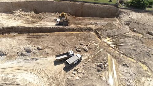 Construction Site Trucks Unloads