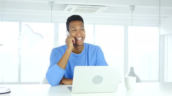 Cover Image for Afro-American Man Talking on Phone, Attending Call at Work