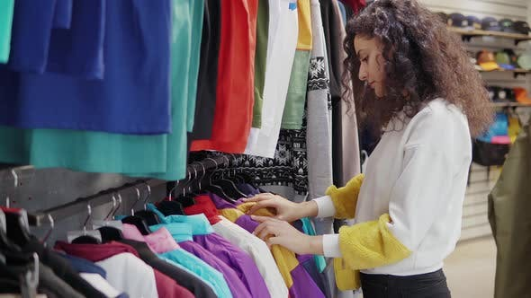 Woman in a Boutique Picking Clothes