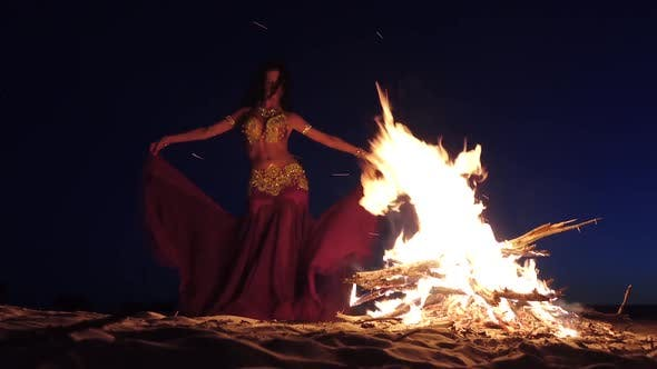 Thumbnail for Night the Girl Dances Belly Dancing on the Sand, She Has a Bright Outfit