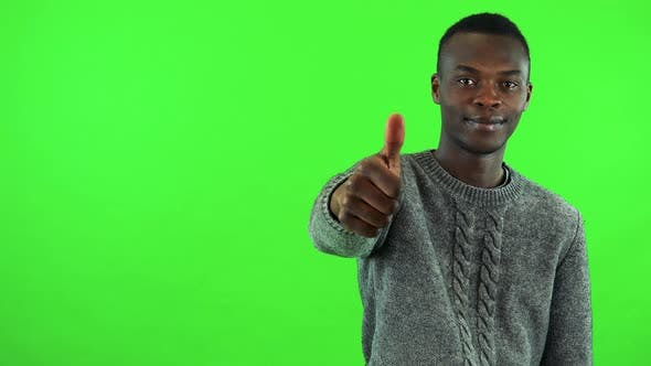 Thumbnail for A Young Black Man Smiles and Shows a Thumb Up To the Camera - Green Screen Studio