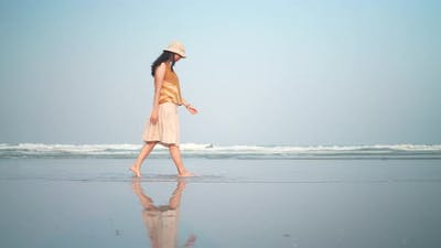 Asian woman walking slow-motion on the beach, summer vacation on the tropical sea beach