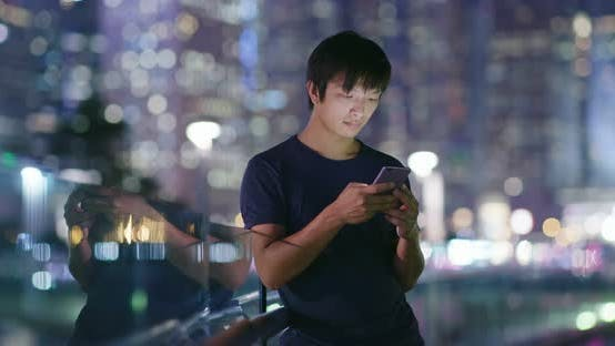 Thumbnail for Man use of cellphone in city at night