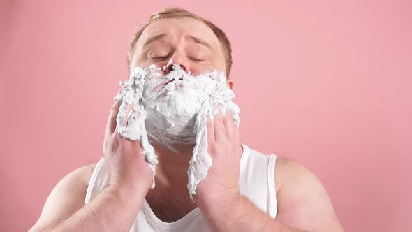 Thumbnail for Funny Fat Middle-aged Man in T-shirt While Applying Facial Shaving Foam, Slow Motion