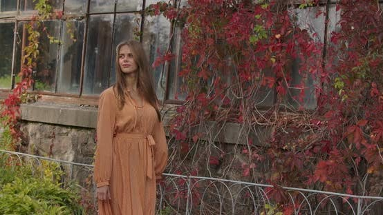 Thumbnail for Beautiful Brunette Caucasian Woman Walking By Building Covered with Red Leaves, Looking Aroung