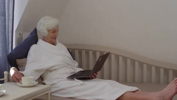 Thumbnail for Graceful Relaxed 70-Something Lady Reading Good News on Laptop in Hotel