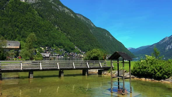 Thumbnail for Small Wooden Bridge on the Lake in Front of Hallstatt Village - Mountains with Trees