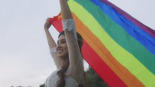 Asian Lesbian Girl Raising LGBT Rainbow Flag In The Park.