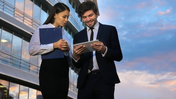 Thumbnail for Business couple looking at business results on digital tablet.