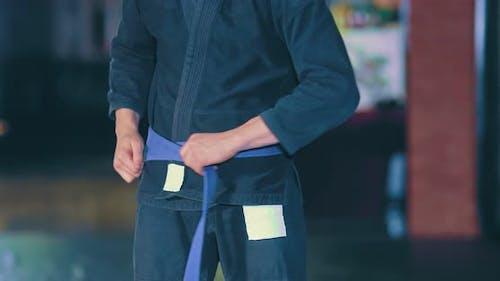 Athlet in einem Kimono bindet einen Knoten in seinem Gürtel