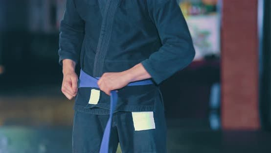 Athlete in a Kimono Is Tying a Knot in His Belt