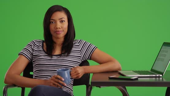 Thumbnail for Portrait of woman sitting at table with laptop holding coffee on greenscreen