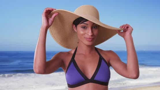 Thumbnail for Beautiful black woman with sunhat on the beach enjoying the sun