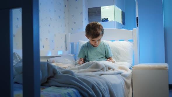 Kleiner 5-jähriger Junge, der auf einem Tablet-Computer benutzt und spielt, bevor er nachts schlafen geht