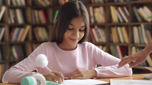 Happy Indian Latin Kid School Girl Pupil Studying at Home with Mom or Tutor