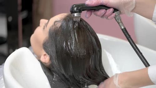 Beautician Rinsing Hair of Client