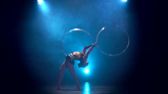 Thumbnail for Acrobat Movements with Hoops. Blue Smoke Background