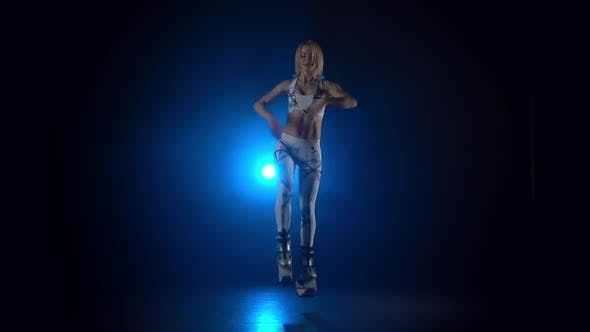 Thumbnail for Woman Dancing in Kangoo Jumps Shoes Against Blue Spotlight. Slow Motion