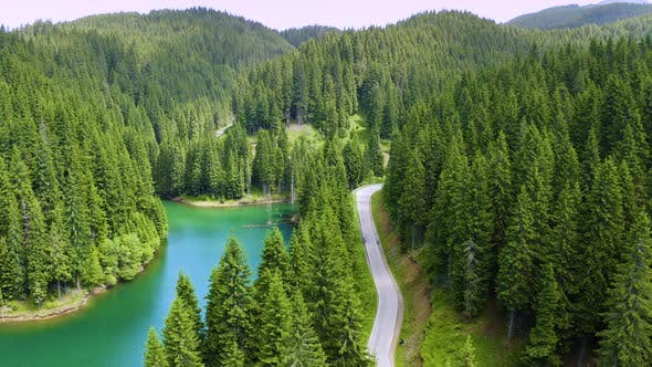 Thumbnail for Aerial view of car driving through the fores and the lake on the side. Beautiful mountain road.