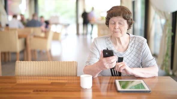 Thumbnail for Senior Woman Using Phone While Thinking At The Coffee Shop