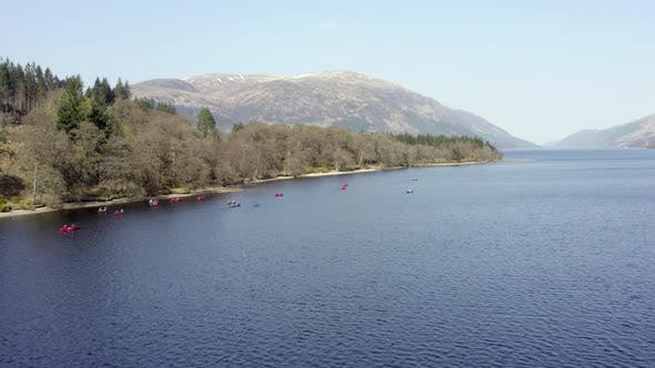 Canoeists in Scotland in a Loch Surrounded by Beautiful Landscape