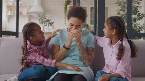 Mischievous Mother Joking with Little Girls on Sofa