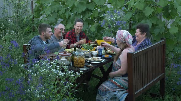Cover Image for Gathered together relatives and friends at picnic outdoor. Family dining together and having fun.